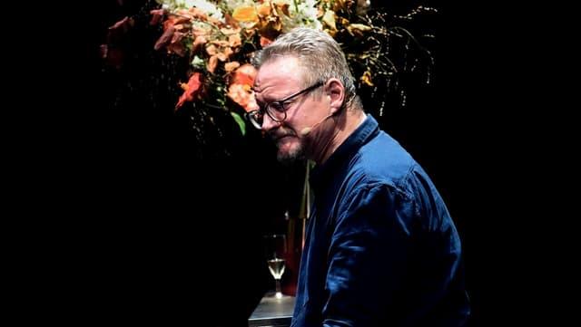 ein Mann sitzt vor einem Blumenstrauss