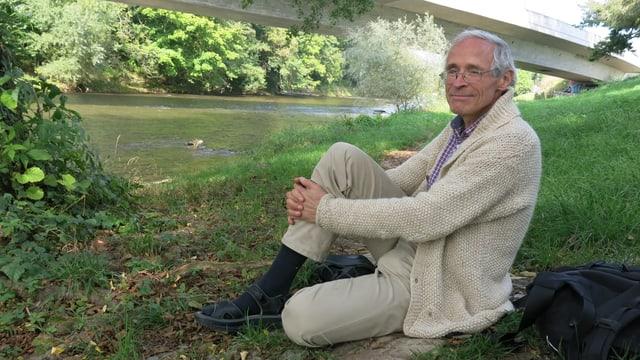 Martin Vosseler sitzt an der Wiese, hinter ihm die fertig gebaute Zollfreistrasse.