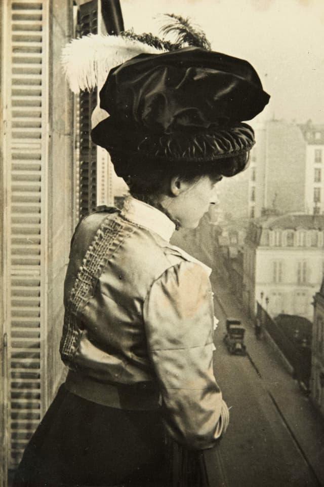 Alte Schwarzweissfotografie: Junge Frau mit der Federhut auf einem Balkon.