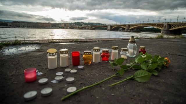 Kerzen an einem Flussufer und eine Brücke im Hintergrund.