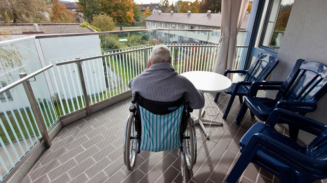 Eine Person sitzt auf dem Balkon im Rollstuhl