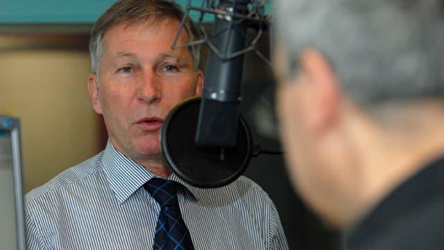 Alsfred Schmid spricht ins Mikrofon des Studios in Aarau, er trägt eine Krawatte und ein Hemd, im Gegenüber steht Regionaljournal-Redaktionsleiter Andreas Capaul, mit dem Rücken zur Kamera.