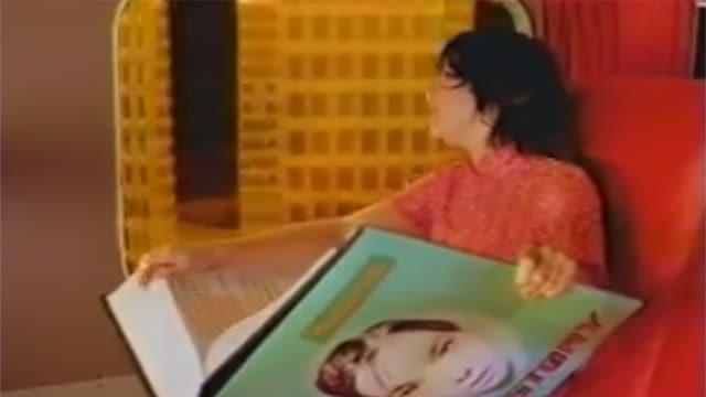 Eine Frau mit einem Riesenbuch auf den Knien fährt Zug.