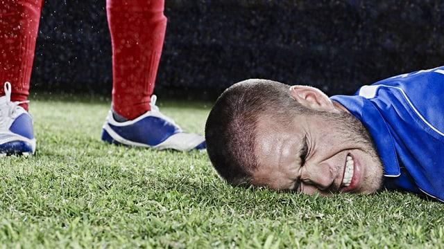 Ein Fussnballer liegt mit schwerzverzerrtem Gesicht auf dem Rasen.