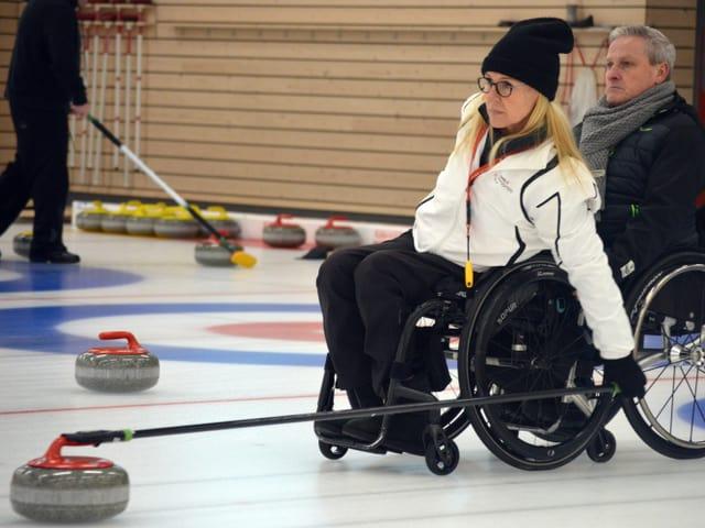 Eine Frau mit Rollstuhl hält eine lange Stange mit einem Curlingstein am Ende in den Händen.