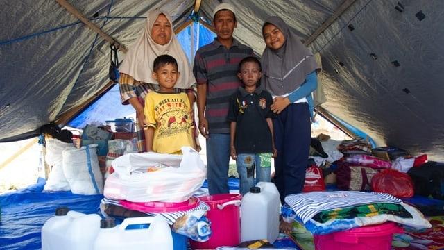 Famiglia da l'Indonesia en tenda cun rauba ord donaziuns.