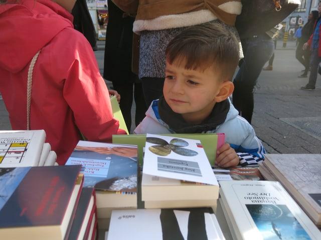 Nahaufnahme eines kleinen Jungen, der sich Bücher ansieht.