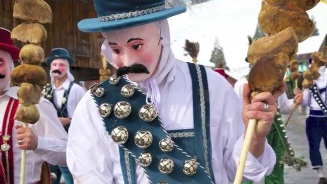 Eine Fasnachtsfigur mit Hut und Schellengurt.