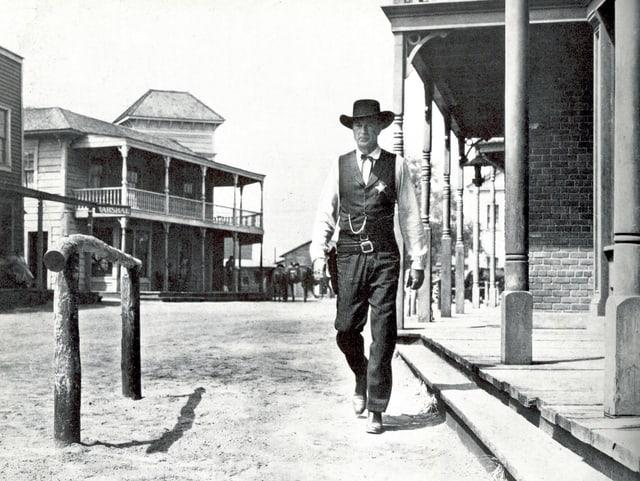 Town Marshals Will Kane läuft die Strasse herunter.