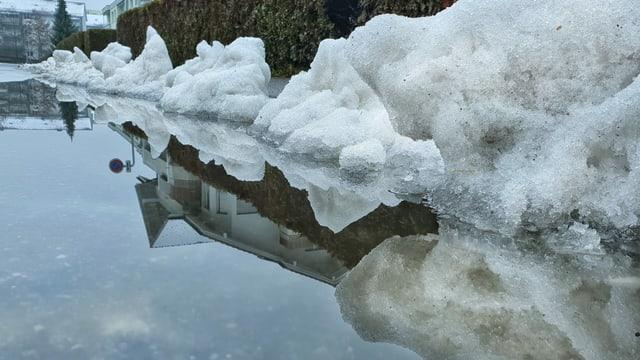 Schneereste und gestautes Wasser auf Strasse.