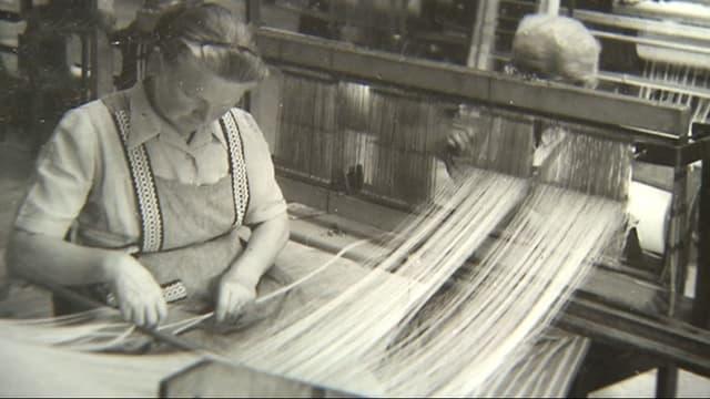 Schwarzweissbild einer Arbeiterin an einer Textilverarbeitungsmaschine.