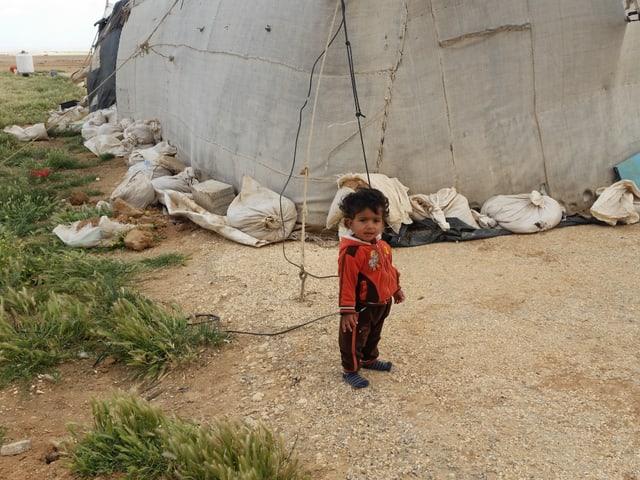 Kleines Kind ohne Schuhe vor der Unterkunft.