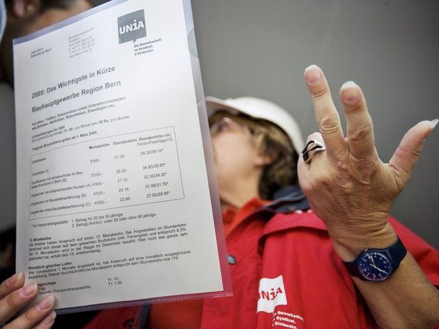 Unia-Frau hält eine Formular in der einen Hand und gestikuliert mit der andern.Ihr Gesicht sieht man kaum.
