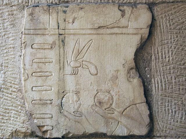 Steintafel mit Abbildung von Bienen und Krügen.