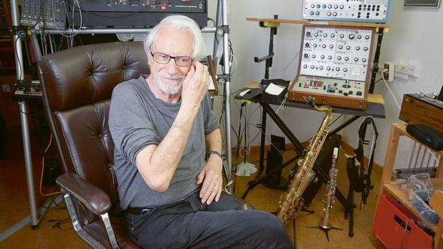 Ein älterer Mann sitzt in einem Tonstudio.