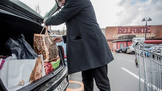 Mann packt auf einem Parkplatz vor einem Einkaufszentrum seinen Kofferraum voll mit Einkaufstaschen.