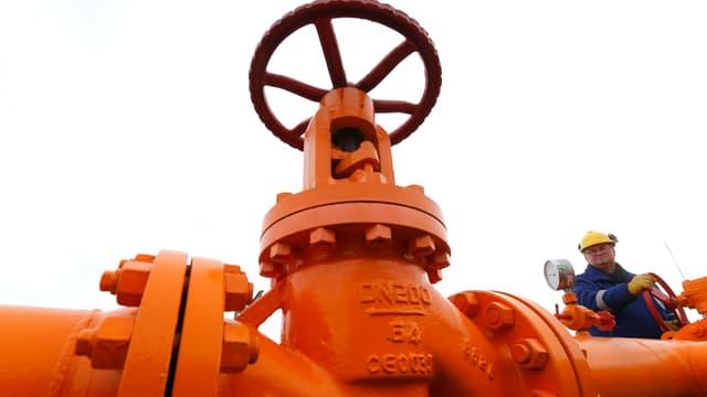 Ein Mann steht neben einer grosser oranger Gas-Leitungsanlage mit Handventil.