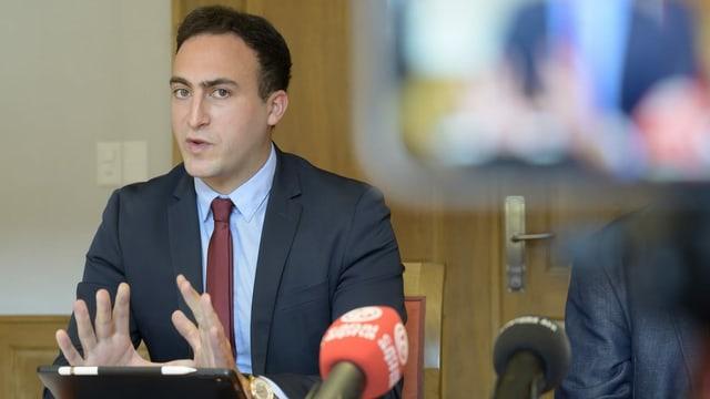 Valentin Zuber spricht gestikulierend und mit ernster Miene zu den Medien.