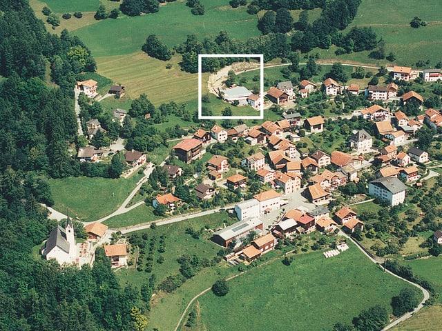 Vista da Tumegl. L'areal da Sogn Murezi sa chatta amez in quartier da chasas novas.