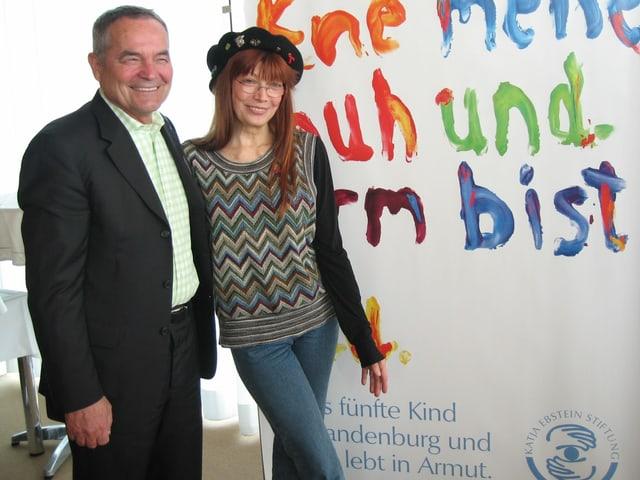 Katja Ebstein vor dem Plakat ihrer Kinderstiftung. Der Schriftzug sieht aus, als ob er mit Fingerfarben gemalt wurde.