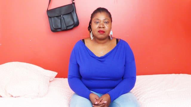 Thelma Chikwanha sitzt auf einem Bett.