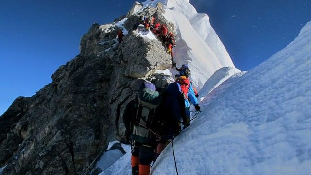 Bergsteiger mit dem Rücken zur Kamera vor dem Hillary Step, an dem sich eine Schlange von andern Besteigern hocharbeitet