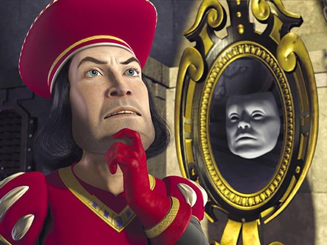 Ein Mann mit rotem Hut steht neben einem Spiegel, in dem ein graues Gesicht zu sehen ist.