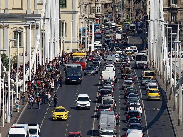 Auf der Brücke marschieren die Flüchtlinge neben fahrenden Autos.