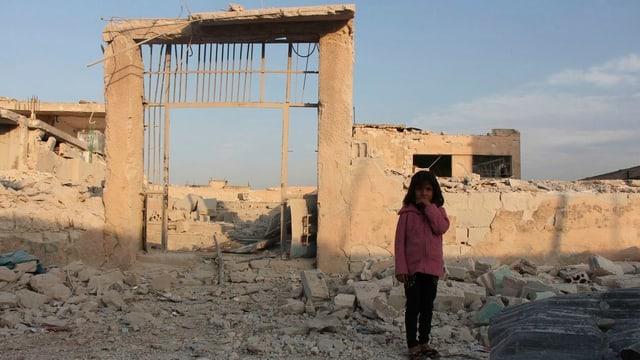 Ina matta davant da ruinas en Siria.