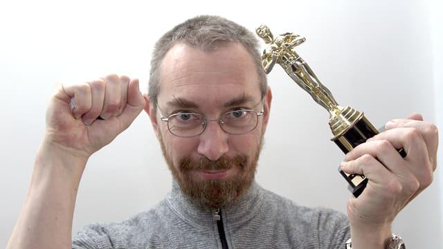 SRF-Filmredaktor mit einer Oscar-Figur in der Hand und geballter Faust.