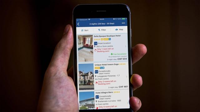 Ein Smartphone-Bildschirm zeigt Suchresultate der Seite Booking.com an.