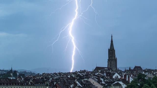 Blitz über der Stadt Bern mit der Silhouette des Münsters