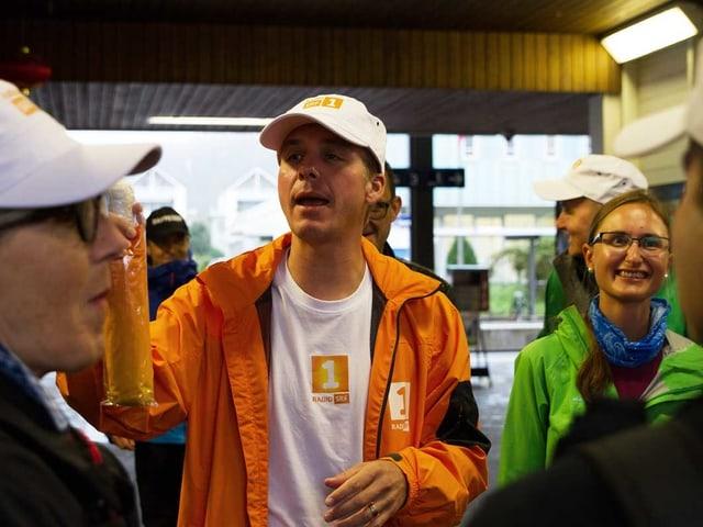 Reto Scherrer steht mit einem Schirm in der Hand in der Gruppe.
