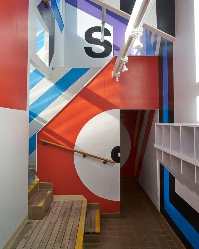 Grossformatige Grafik in einem Innenraum mit Treppe.