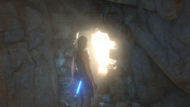 Lara Croft steht im Dunkeln vor eine Öffnung, durch die Licht scheint.