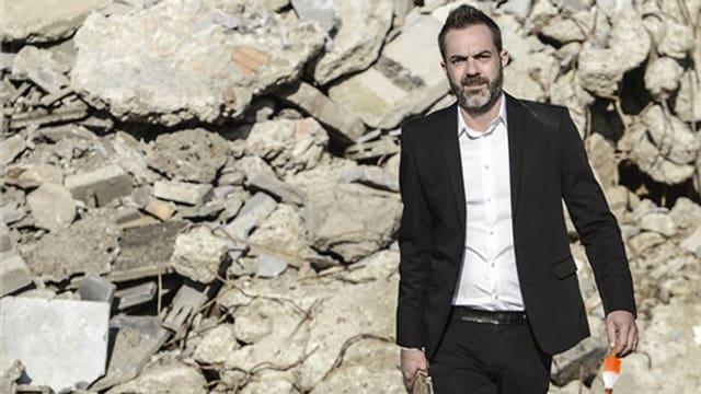 Mann vor einer Wand aus Steinen.