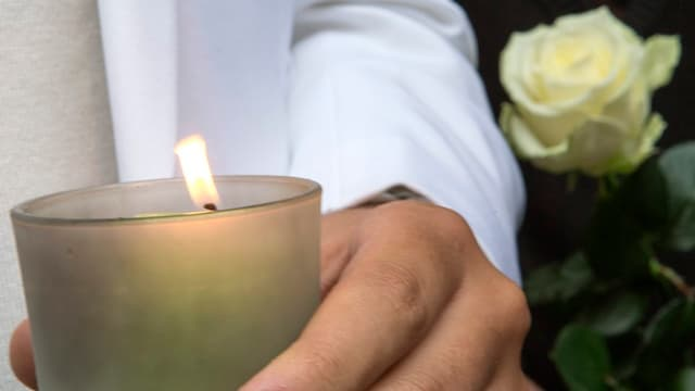 Kerze mit Rose an Gedenkmarsch.