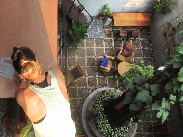 Maja Hürst arbeitet draussen auf dem Dach, unter ihr ein Innenhof mit Stühlen und einem grossen Baum.