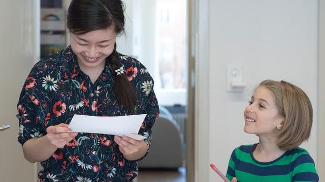 Ein frau schaut lachend auf einen Zettel, ein Mädchen steht lachend daneben und schaut ihr zu.