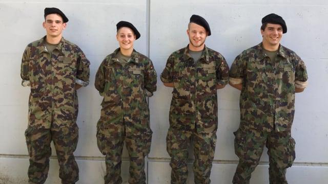 Vier Rekruten stehen im Tenue an einer Wand.