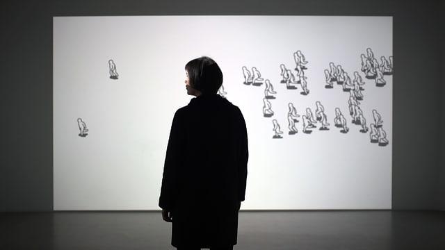 Eine Person steht vor einer Leinwand, auf der gezeichnete Figuren herumrennen.