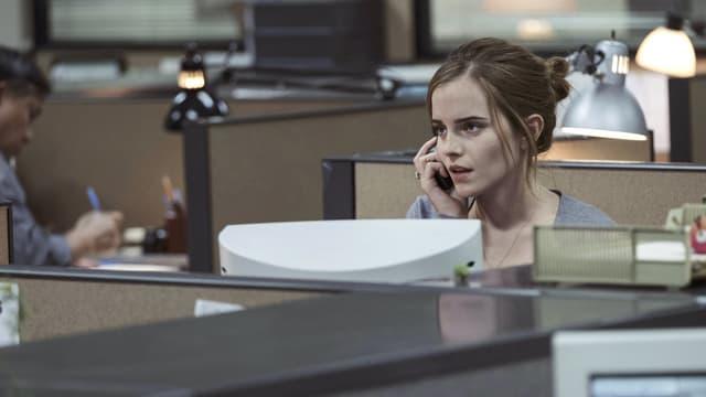 Mae (Emma Watson) sitzt telefonierend im Büro.