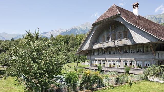 Ein altes Schweizer Bauernhaus mit einem Garten mit Baum.