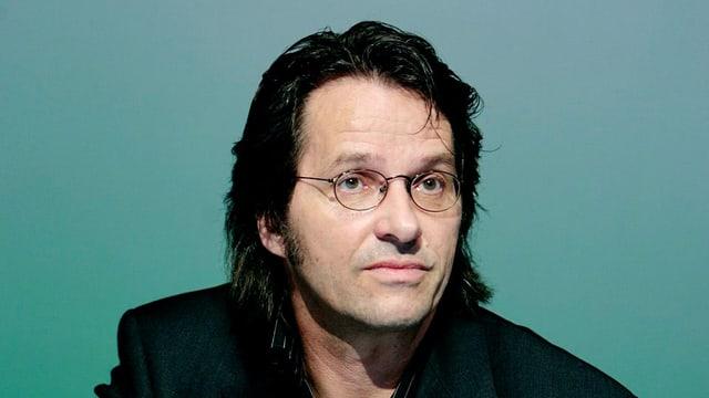 Ralf Rothmann in schwarzem Anzug, mit Brille.