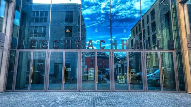 Eingang Aeschbachhalle mit spiegelnder Glasfront
