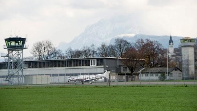 Kleiner Flugplatz mit Rollbahn, Betriebsgebäude, Turm und Flugzeug.