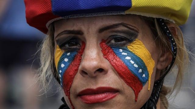Frau mit venezolanischen Farben im Gesicht und Tränen