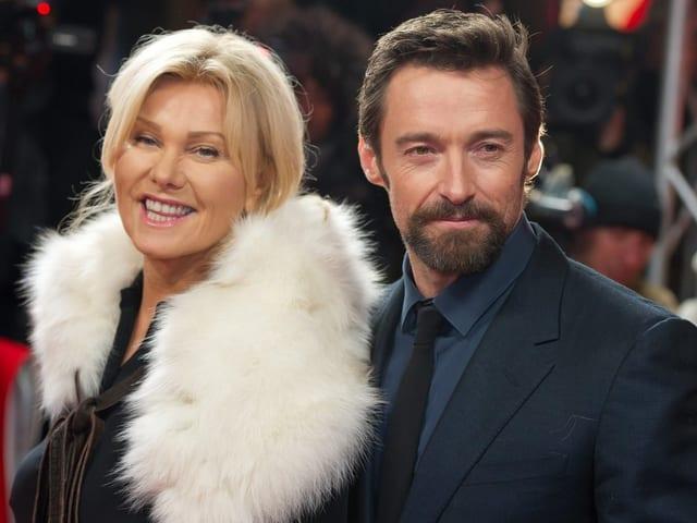Blonde Frau mit weissem Pelz um den Hals steht links neben bärtigem Mann im schwarzen Anzug.