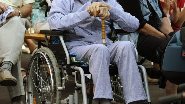 Ein alter Mann sitzt im Rollstuhl und stützt seine Hände auf einen Gehstock