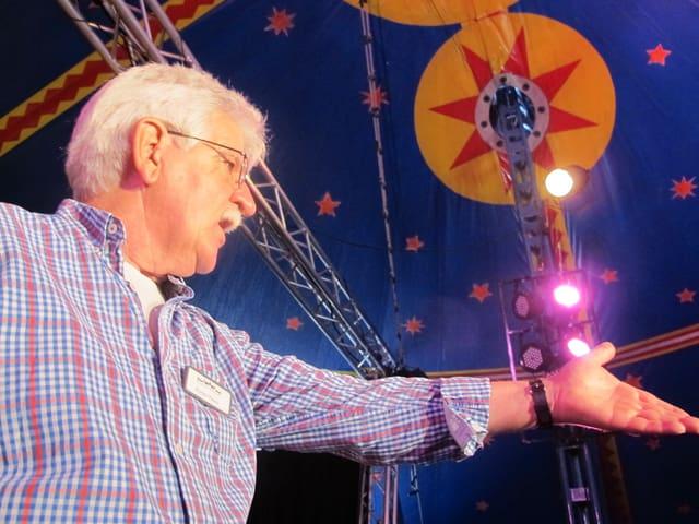 Werner Panzer zeigt auf die Bühne, von unten fotografiert. Über seinem Kopf die Kuppel des Zirkuszeltes mit Bühnenlicht.